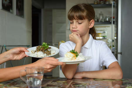 The girl thoughtfully chooses a dish for lunch Standard-Bild