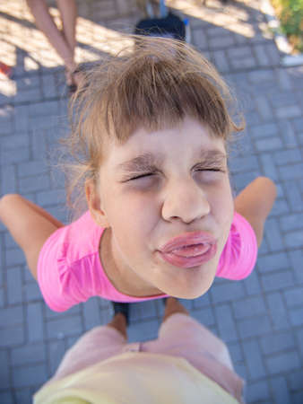 Mischievous girl grimaces and shows a vile muzzle with a tongue