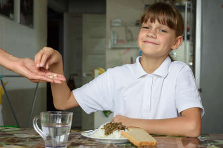Mom's hand holds out two pills to the girl to take before lunch