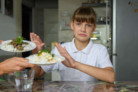 The girl refuses to eat and looks sadly into the frame Standard-Bild