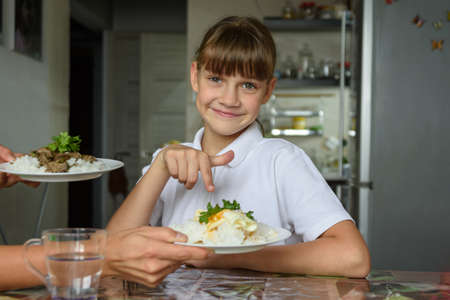Happy girl chose one dish out of two offered by her mother for lunch