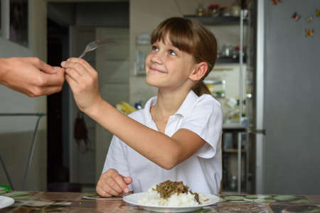 A girl takes a fork from her mother's hand while preparing to dine at the kitchen table