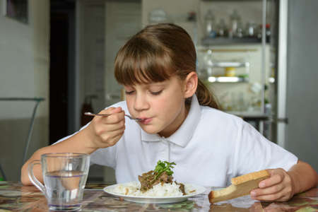 Girl eats the second dish for lunch