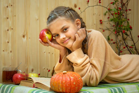 A girl lying down reads a book, a pumpkin and apples lie nearby, a girl joyfully looks into the frame