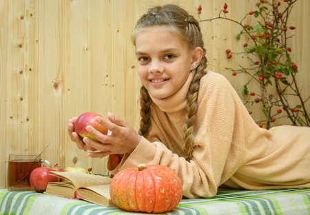 A girl lying down reads a book, holds an apple in her hands and looks happily into the frame Standard-Bild