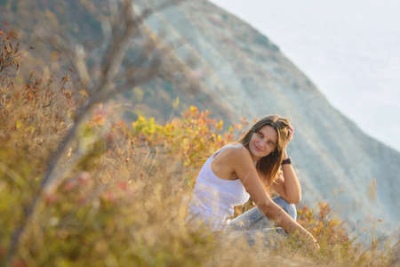 Happy girl sitting on the mountainside and happily looking at the landscape Standard-Bild