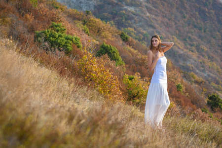 A beautiful slender girl in white clothes stands on the mountainside
