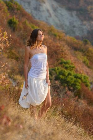 beautiful girl in white dress walking on the mountainside