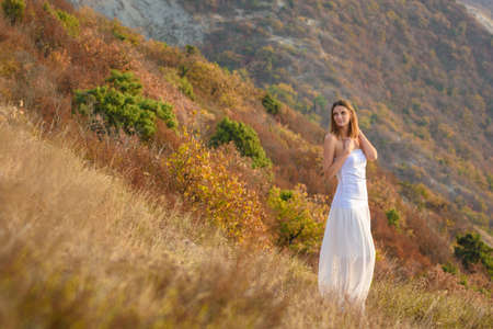 Beautiful slender girl in white clothes on the background of a beautiful mountain landscape
