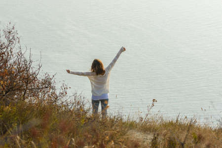 Happy girl happily raised her hands up enjoying the seascape, view from the back