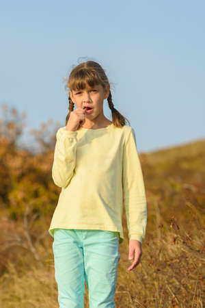 The girl nibbles on a lollipop and looks at the frame with a puzzled look Standard-Bild