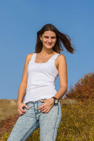 Portrait of a beautiful girl in a white T-shirt and jeans in the rays of the setting sun Standard-Bild