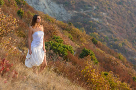 A girl in a white dress walks on a hillside