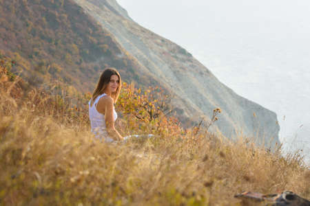 The girl is sitting on the mountainside and turning around looked into the frame