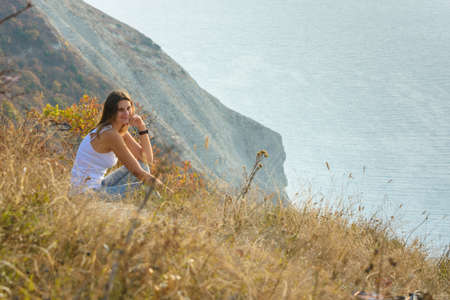 The girl sat down on the mountainside and looks at the seascape Imagens