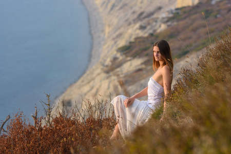 A beautiful girl in a white dress enjoys a beautiful view from the mountain to the sea at sunset Standard-Bild