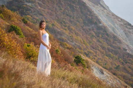 A beautiful girl stands on a hill by the sea