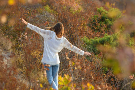 Slender beautiful girl walks through the forest making her hands an airplane, a view from the back