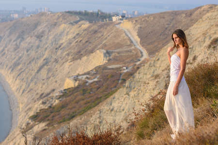 A girl stands on a mountainside at sunset against a beautiful landscape Standard-Bild