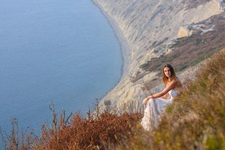 Beautiful girl at sunset sitting on a rocky beach Standard-Bild