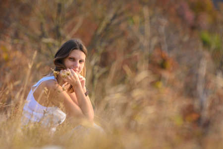 A girl sits in a field, against a background of blurred wildflowers and looks into the frame