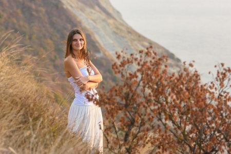 A beautiful girl stands on a rocky seashore and hugs wildflowers Standard-Bild