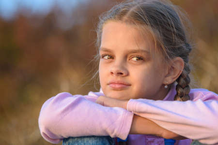 Portrait of a thoughtful beautiful ten-year-old girl at sunset Standard-Bild