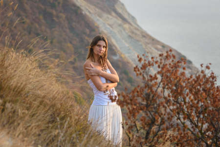 A girl embraces wildflowers on the background of a beautiful mountain and sea landscape Standard-Bild