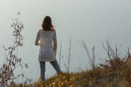 Girl stands on a hill and looks at the sea, rear view