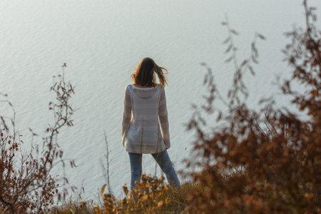 Slender girl standing on the seashore, rear view