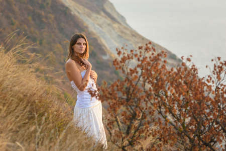 Beautiful girl in white dress hugging wild flowers on the background of beautiful scenery