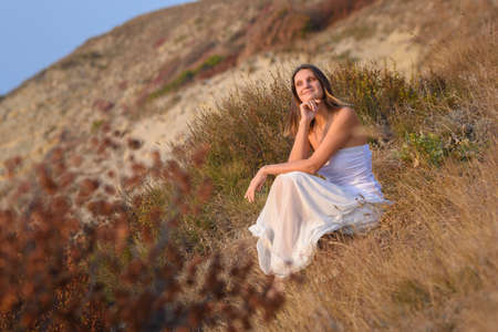 A girl in a white dress enjoys a beautiful view of the sunset