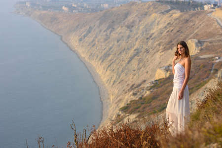 A beautiful slender girl in a white dress stands on a hill and enjoys a beautiful view of the sunset