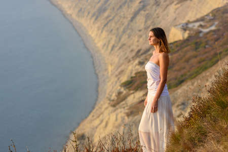 Beautiful slender girl in a white dress on the background of a beautiful mountain and sea landscape Standard-Bild