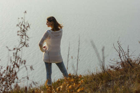 A girl stands on a hill by the sea and looks around, rear view