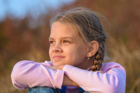 Portrait of a beautiful ten-year-old girl looking at the sunset, close-up