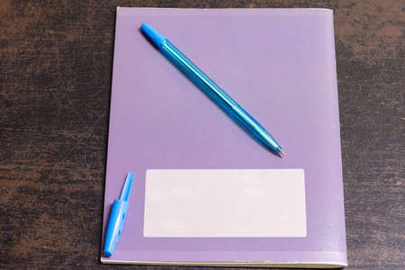 On the old table is a notebook and a pen with an open cap