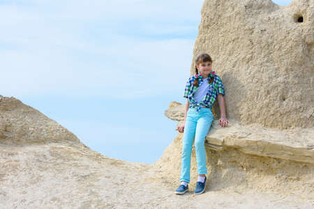 A ten-year-old girl sat down on a rock ledge resting after climbing