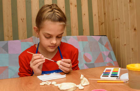 A girl at home paints figures from salt dough
