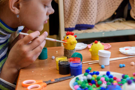 The girl paints crafts from eggs for the Easter holiday