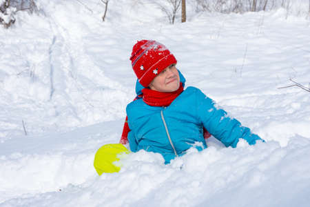 A girl sits in a snowdrift and looks funny at the top of the slide