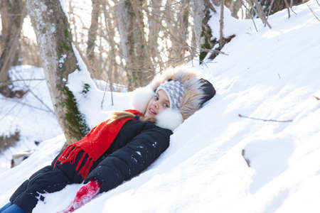 The girl fell into a snowdrift with her back and looked into the frame in a snowy forest