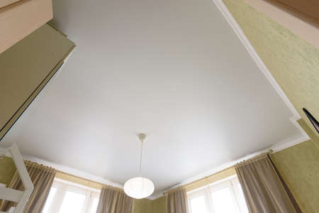 Stretch white matte ceiling close-up with a chandelier in the interior of a living bedroom