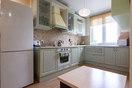 Interior of a modern classic kitchen with a corner kitchen set by the window