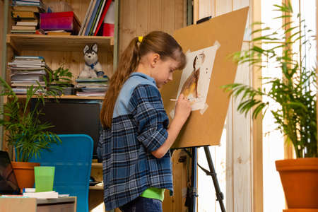 Girl draws a cat on an easel in her room at home