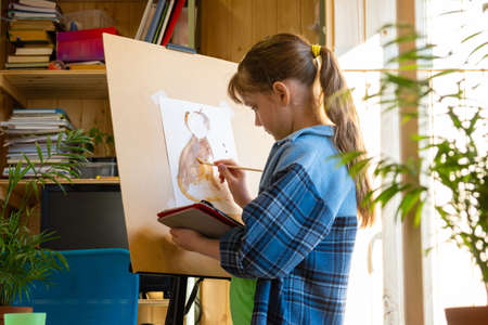 A ten-year-old girl draws with paints on an easel, holding a tablet computer in her hands Standard-Bild