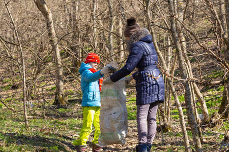 A girl collects garbage in the forest, a girl holds a large garbage bag