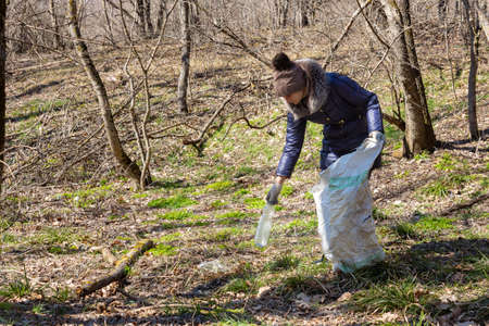 The girl collects garbage in the forest, took a plastic bottle and puts it in a bag