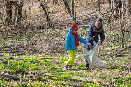 A girl and a woman collect garbage at the forest edge