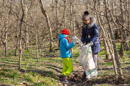 A girl throws a plastic bottle into a trash bag that the girl holds, together they collect garbage in the forest
